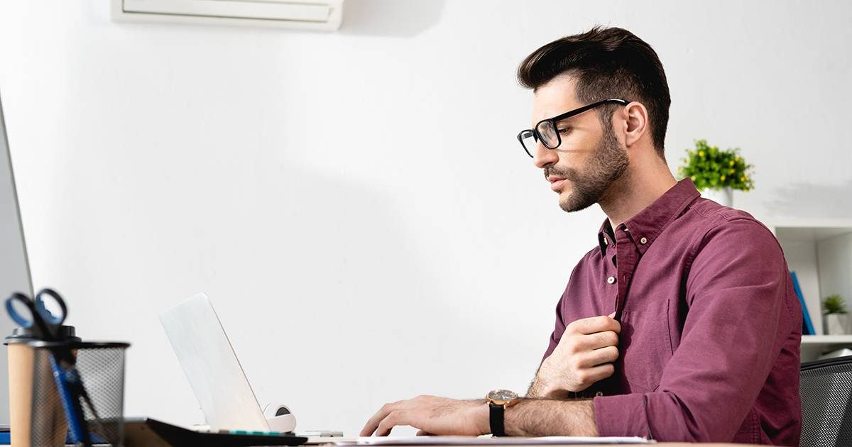 young businessman touching shirt while working on laptop and suffering from heat near air conditioner